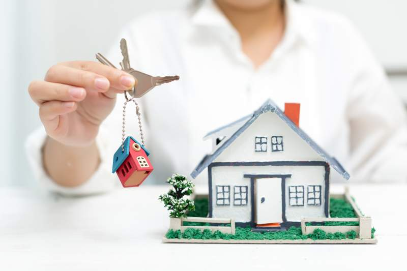 Real-estate-agent-with-house-model-and-keys