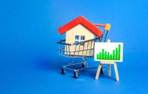A-house-in-a-shopping-cart-and-an-easel-with-a-positive-green-trend-chart