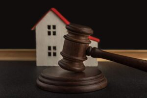 Judges-hammer-on-background-of-model-house