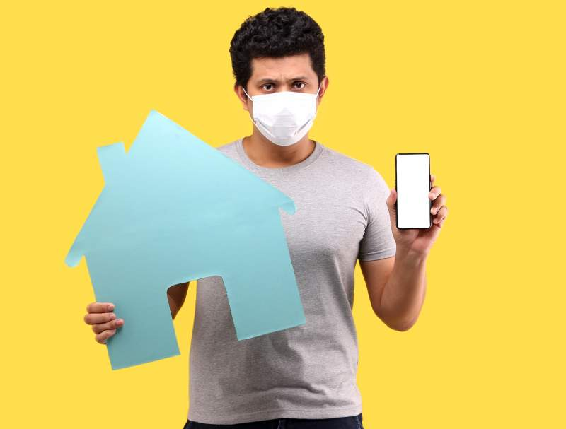 man-wearing-mask-hand-hold-smart-phone-hold-paper-house