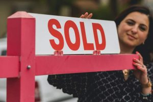 Real Estate Agent Holding a Signage